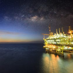 Offshore construction platform for production oil and gas, Oil and gas industry and hard work, Production platform and operation process by manual and auto function. Milky way background and galaxy.